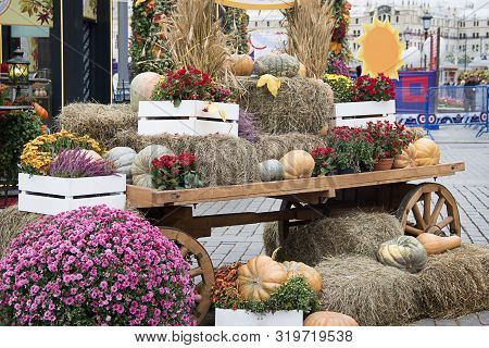 Composition From Pumpkins With Hay, Ears Of Wheat, Cardboard Sun And Flowers On An Old Cart For Autu