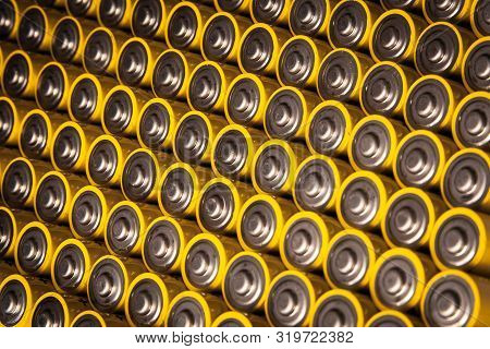 Close view of batteries alkaline 1.5 Volts in size AA Several batteries in rows.A close-up of the same yellow batteries, lined up in even rows by positive charges. An unsafe way to use energy. poster