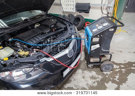 The Procedure For Refueling A Car Air Conditioner Using A Special Device With A Blue Compressor And