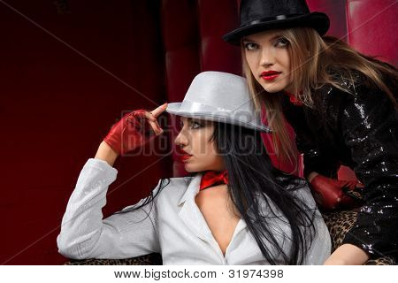 Cabaret performers wearied white and black clothes sitting on armchair