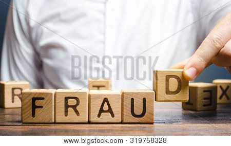 Wooden Blocks With The Word Fraud And Man. Cheating White-collar . The Crime. Theft Of Another's Pro