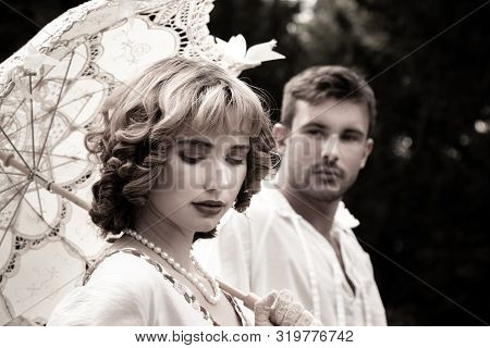 Handsome Young Couple In Vintage Clothing With Beautiful Woman Looking Down As Handsome Man Watches