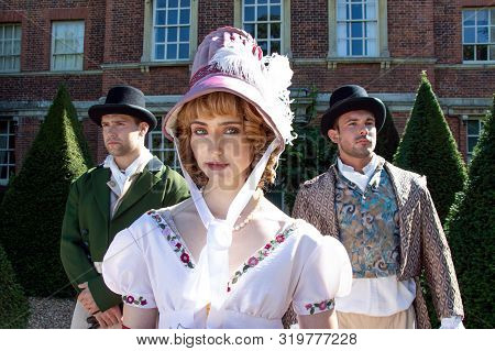 Handsome Male Couple And Beautiful Woman Dressed In Vintage Clothing Standing Outside Of Stately Hom