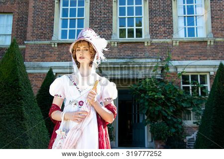 Beautiful Lady Wearing Vintage Regency Dress And Bonnet, Carrying A Parasol And Standing Outside Of