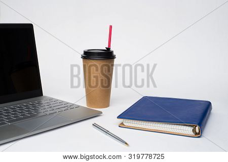 Work Office Desk With A Cup Of Coffee Computer Laptop, Notebook, Pen
