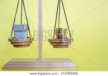 Scales With Imitation Of The House In The Form Of A Metal Keychain And Coins On A Yellow Background.