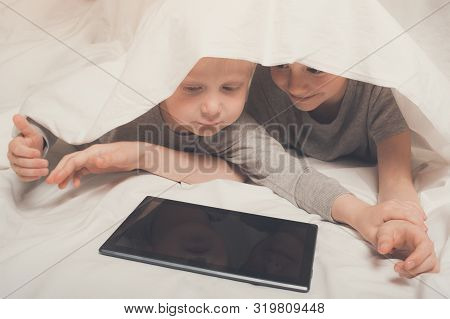 Two Boys Lying And Watching Something On A Tablet, Hid Under The Covers. Gadget Leisure