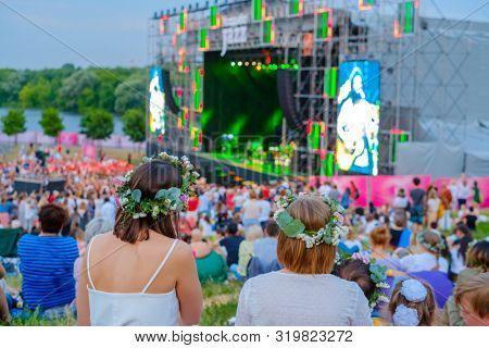 Friends watching concert at open air music festival, back view, stage lights and dancing fan crowd at background