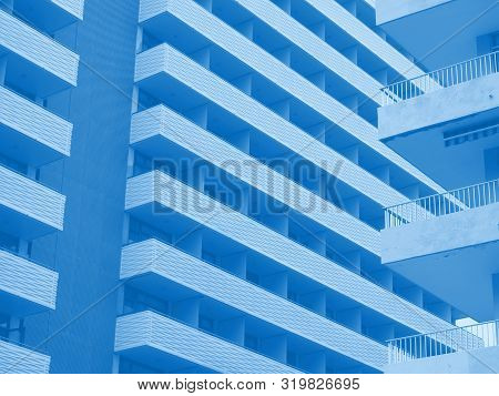 Blue Toned Abstract Image Of Large Modern Highrise Modern Apartment Buildings With Angular Balconies