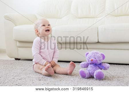 Childhood, Babyhood And Children Concept - Happy Little Baby Girl Sitting On Floor At Home