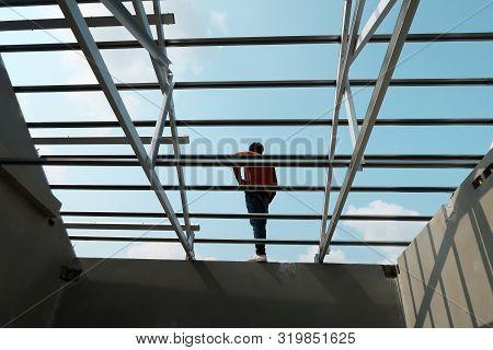 Structure Of Steel Roof Frame For Building Construction On Sky Background. Worker Roofer Builder Wor