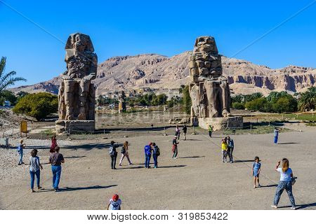 Luxor, Egypt - December 11, 2018: Tourists Taking A Photo Of Memnon Colossi (statues Of Pharaoh Amen