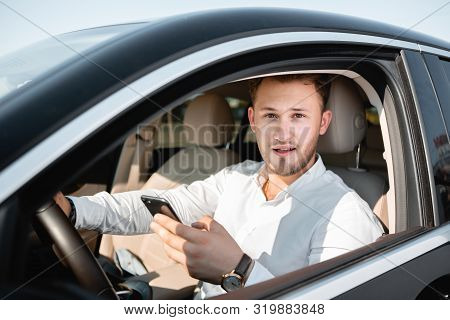 Young Businessman Smiling Looking At Mobile Phone While Driving A Car.