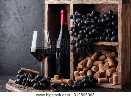 Bottle Of Red Wine With Dark Grapes And Corks Inside Vintage Wooden Box On Black Stone Background. E
