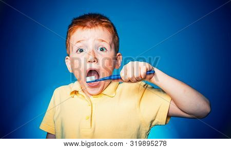 Funny Child Clean Teeth With Toothbrush. Kid With Toothbrush Isolated On Blue Background. Red-haired