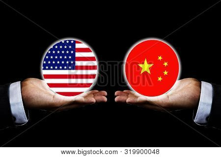 Usa Flag And China Flag  On Hand Of Businessman With Black Background. It Is Symbol Of Economic Tari