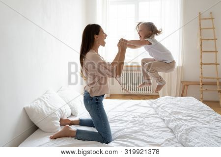 Little Daughter Frolics Jumping On Bed Holding Mothers Hands