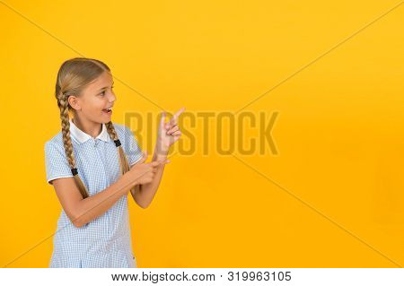 Just Look At This. Happy Little School Girl Pointing Finger At Yellow Background Copy Space. Back To