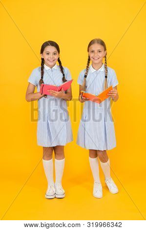 encyclopedia book for children. small girls love literature. old school. happy friends in retro uniform. vintage kid fashion. back to school. small girls hold workbook and notepad. with lesson book. poster
