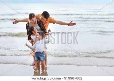 Happy Asian Family Dad And Mom With Their Children Boy And Girl Raising Hands With Happy Smiling Fac