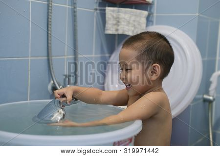 The Child Is Bathing In The Bathroom, Showing A Happy Face.