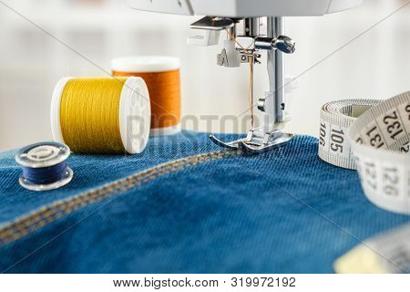 Sewing Denim Jeans With Sewing Machine. Close Up Of Needle Of Sewing Machine On The Denim Fabric Sti
