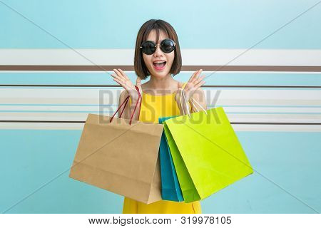 Portrait Of Beautiful Girl Wearing Dress And Holding Shopping Bags.