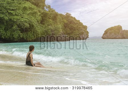 Young Woman Sitting Alone On The Beach Looking At The Sea And Sky.