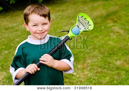 Happy young child lacrosse player with his stick