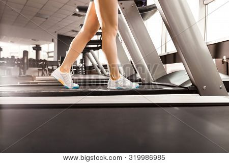 Close Up Womans Legs Walking At The Treadmill In The Gym Over Sunrise. Wearing In White Orange Blue