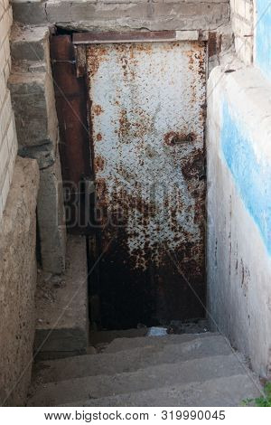 Rusty White Iron Door To The Basement From The Street. Emergency Exit. Corrosion Of Metal. Poverty,