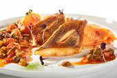 Pike perch or zander fillet with a side dish of tomatoes and capers served on a round platter. Restaurant main course with fried sander fish or barbecue pike meat on white plate isolated poster