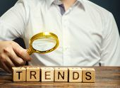 Wooden blocks with the word Trends and businessman with a magnifying glass. Popular and relevant topics. New ideological trends. Recent and latest trend. Evaluation methods. poster