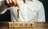 Wooden blocks with the word Trust and keys in the hands of a businessman. Entrust apartment, car, property and real estate. Credit rating. Guarantee for rent. Reliable partner poster