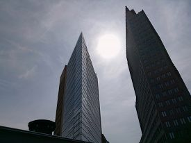Two Tall Buildings Against The Sky With A Bright Sun. Berlin. May 2018