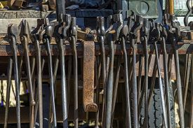 Row Of Heavy Blacksmith Tools Hanging On Rack