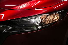 Red Car Headlights. Exterior Detail. Close Up Detail On One Of The Led Headlights Modern Car.