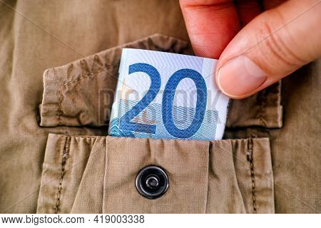 Woman Hand Taking Twenty Euro Bill Out Of The Pocket Of A Beige Jacket. Close-up