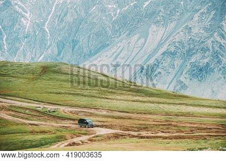 Black Suv Car On Off Road In Spring Mountains Landscape In Georgia. Drive And Travel Concept. Landsc