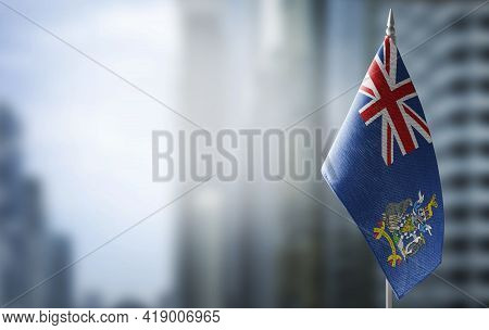 A Small Flag Of South Georgia And The South Sandwich Islands On The Background Of A Blurred Backgrou