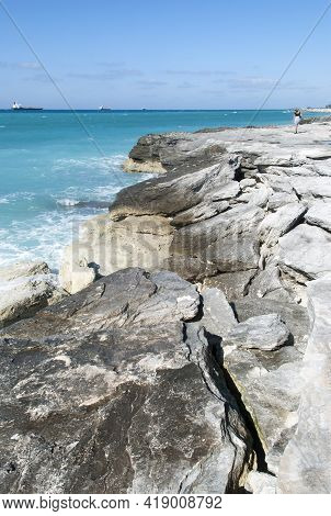The View Of Eroded Broken Coastline On Grand Bahama Island With Cargo Ships In A Background.