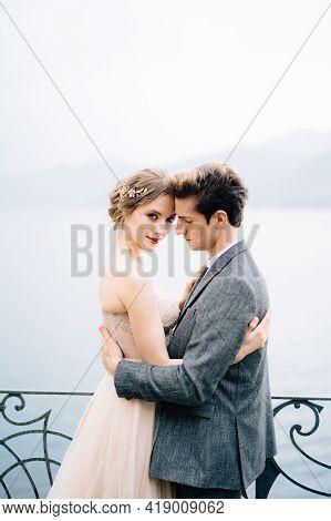 Newlyweds Hug Near A Wrought-iron Fence Against The Backdrop Of Lake Como. Close Up