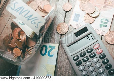 Money Saving Jar, Euro Coins And Bills And A Calculator On A Table - Save Money Concept