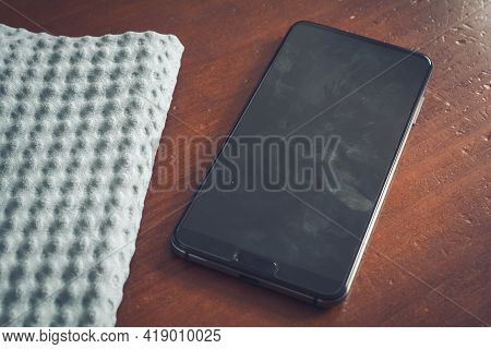 Cleaning Wipe And A Smartphone Screen With Dust, Dirt And Fingerprints On A Table