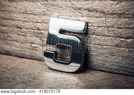 Chrome Number 5 Leaning On A Wooden Wall