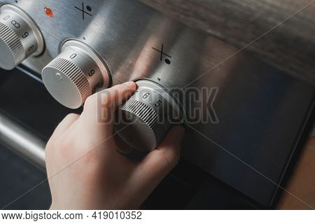 Hand Of A Child Switching On Stove Controls - Prevent Child Hazard Concept