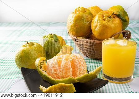 Orange Ponkan, Orange Ponkan Open On A Black Plate, Plus Some Oranges And A Glass Of Juice On A Chec