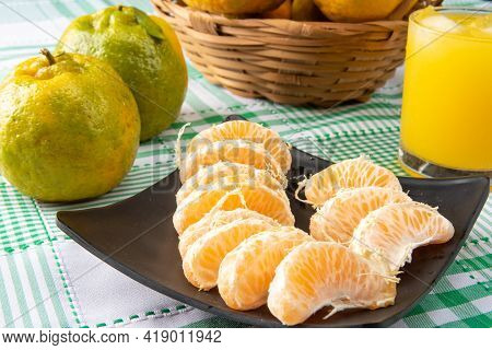 Orange Ponkan, Orange Ponkan Slices On A Black Plate, Plus Some Oranges And A Glass Of Juice On A Ch