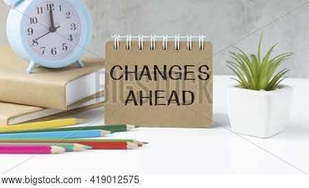 Text Changes Ahead On Brown Paper Notepad On The Table With Diagram. Business Concept