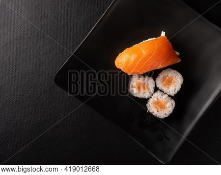 Sushi, Beautiful Arrangement Of Sushi Made On Black Plate On Dark Surface, Black Background, Top Vie